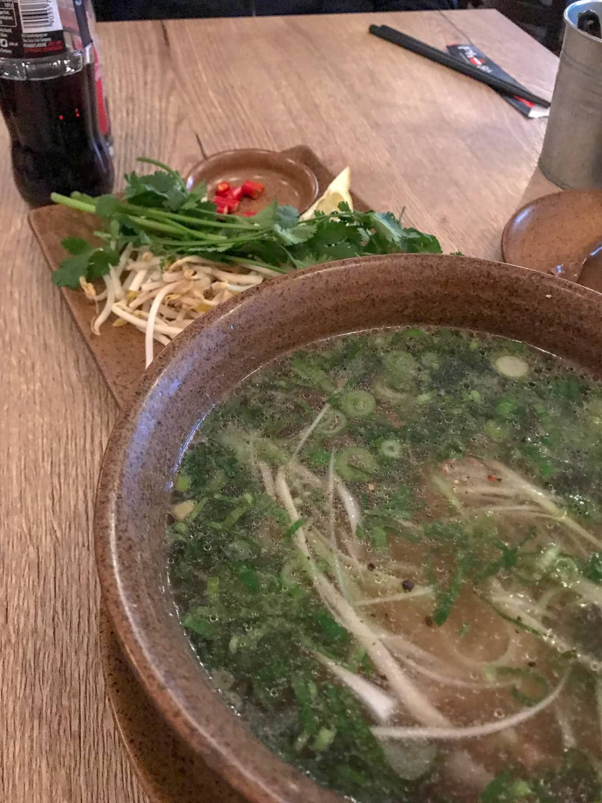 A brown bowl of Vietnamese pho noodles. In the background is a small plate with bean sprouts, coriander and chilli