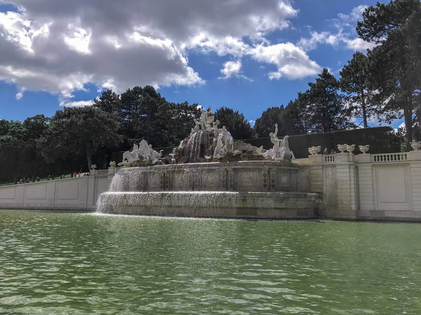 A large fountain with sculptures, water going into the man-made pond below. There are trees in the background and the sky is bright blue.