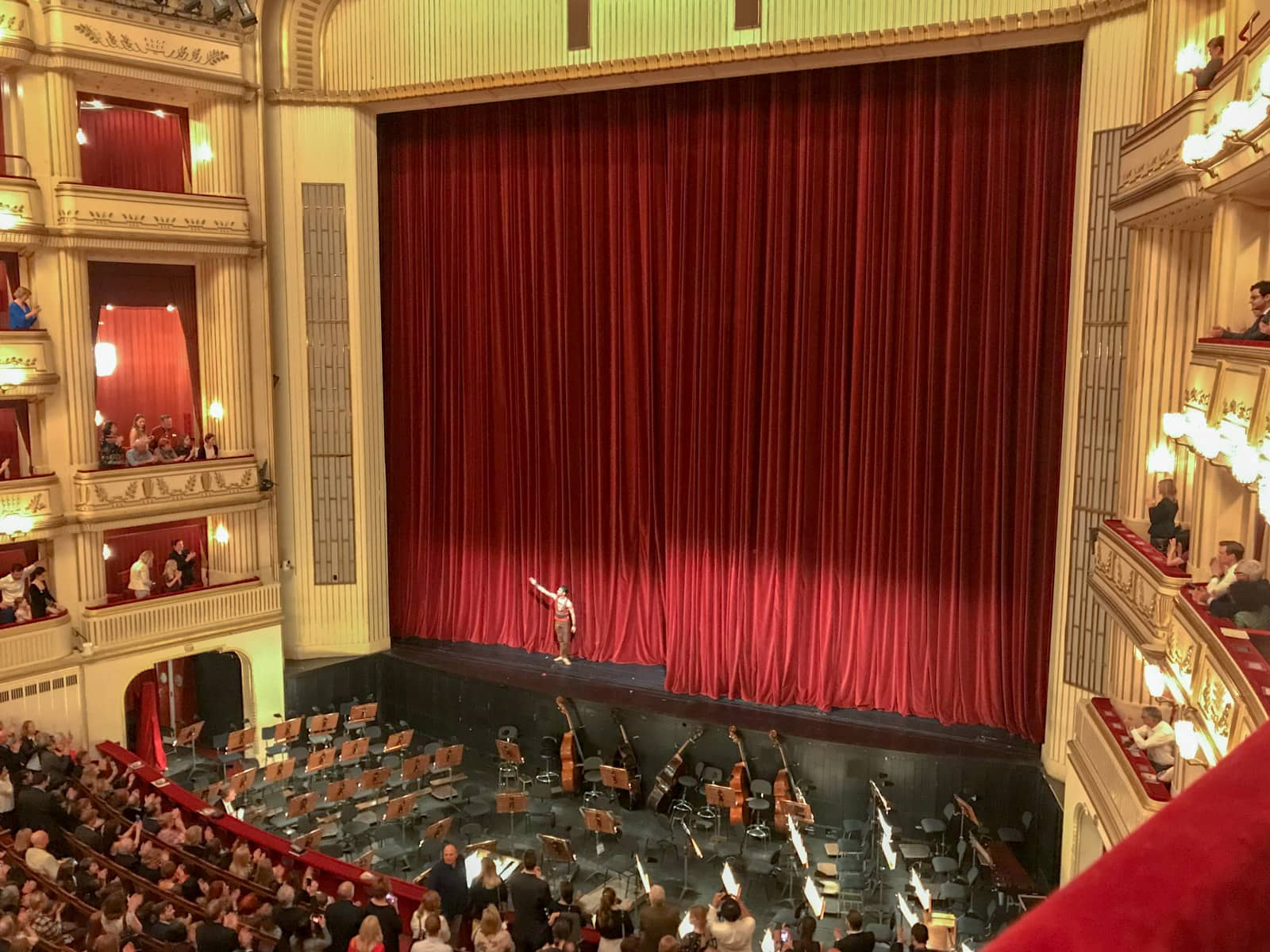 A theatre seen from a box seat. It is the end of a show, and a red curtain is up on the stage. There is one performer taking a bow. The orchestra area is empty.