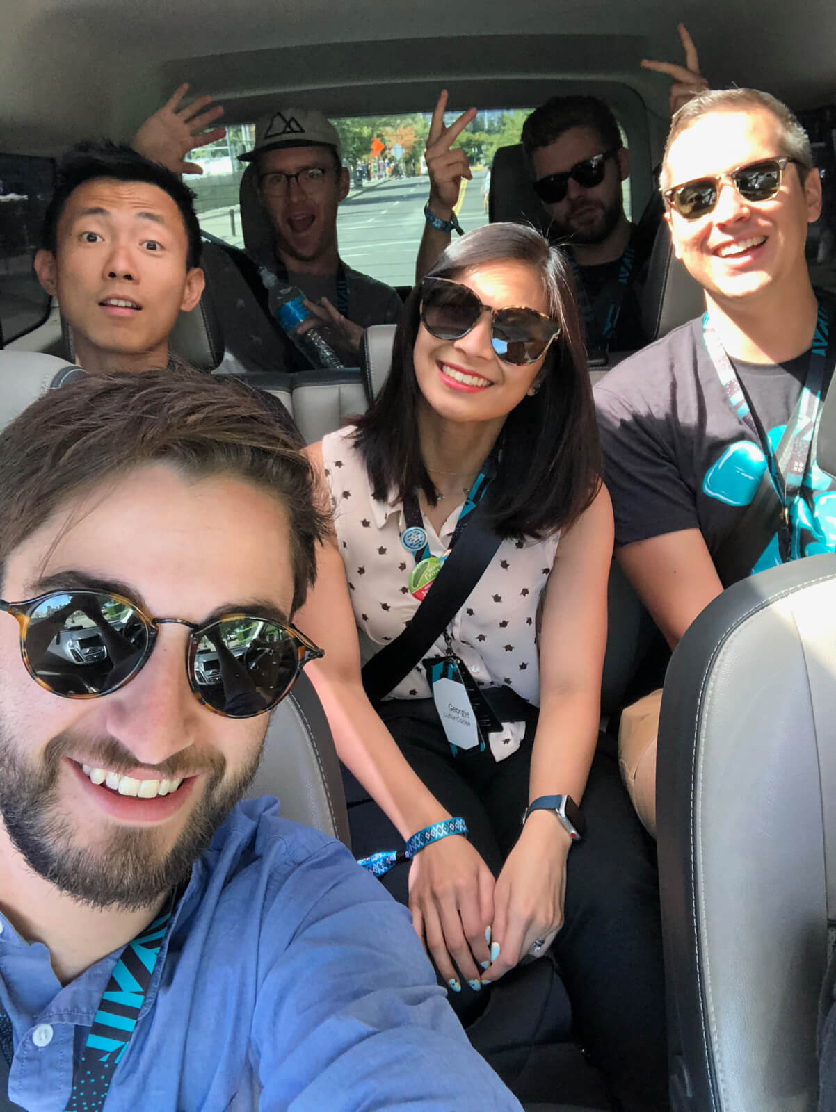 A selfie taken in a car, taken by the man in the passenger seat. There are three people in the second row and two people in the back of the car
