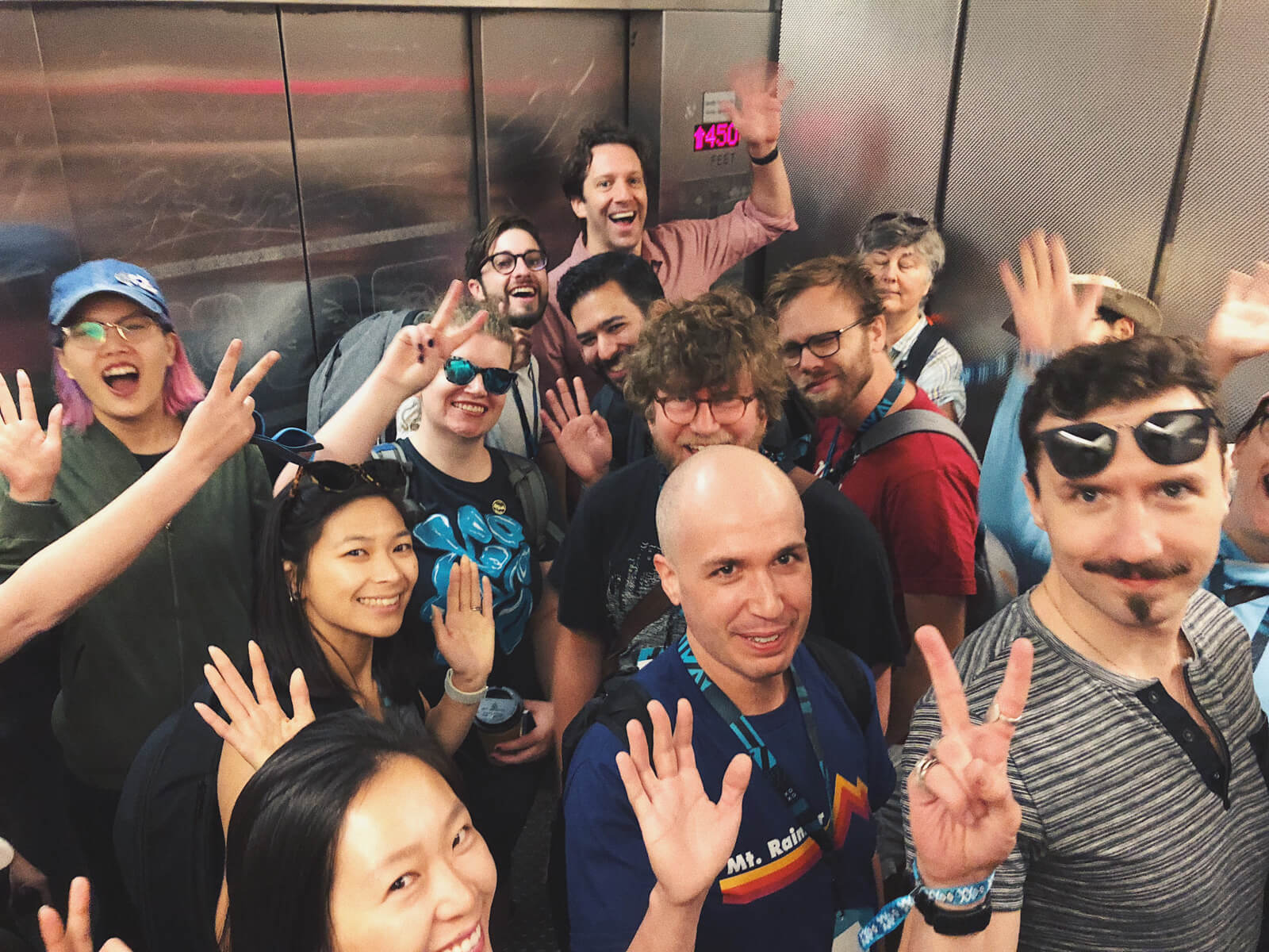 A handful of people in an elevator, all of them smiling/waving.