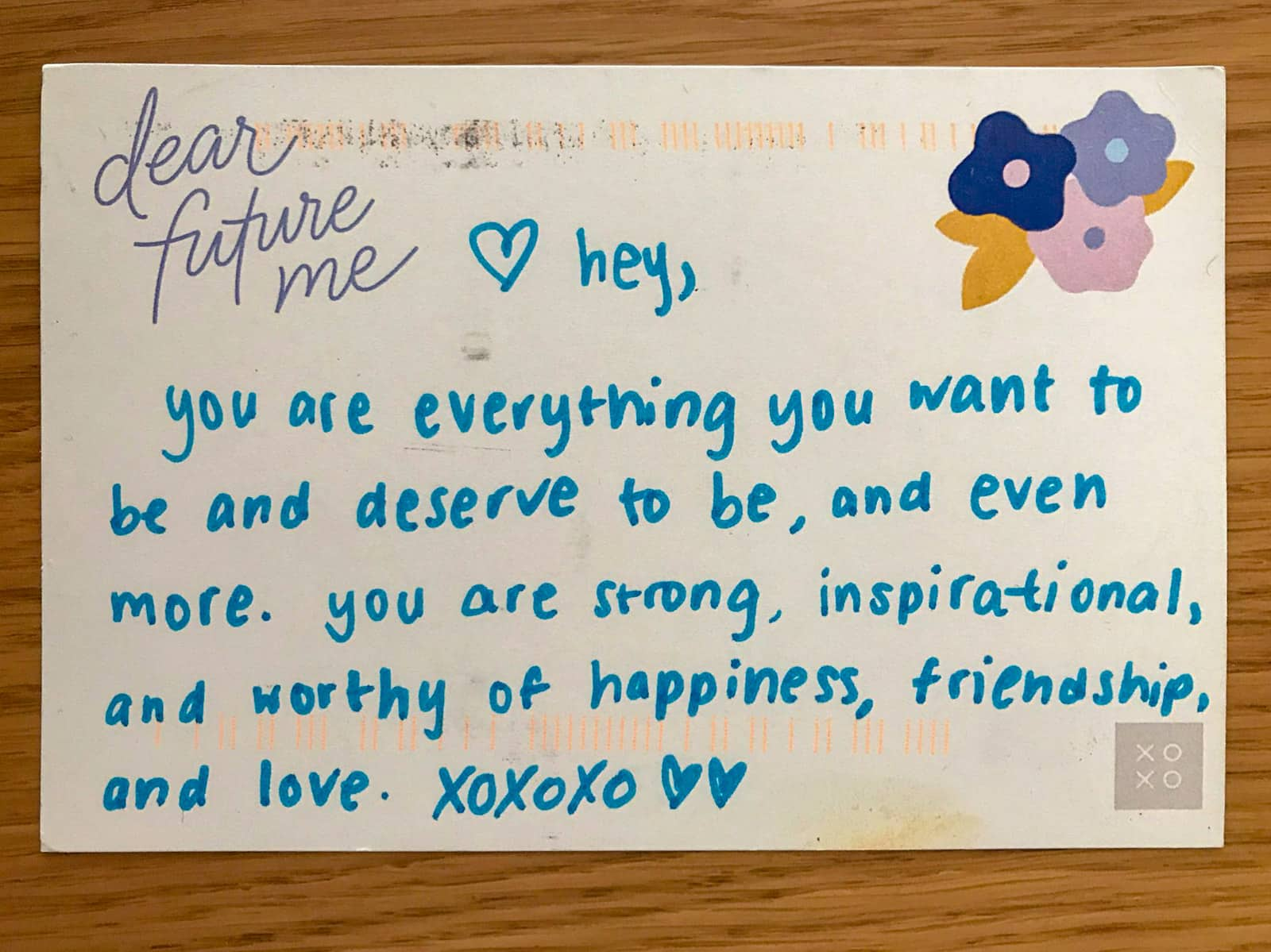 "A postcard with ""dear future me"" printed on it and a handwritten message in blue ink: hey, you are everything you want to be and deserve to be, and even more. you are strong, inspirational, and worthy of happiness, friendship and love. xoxoxo"