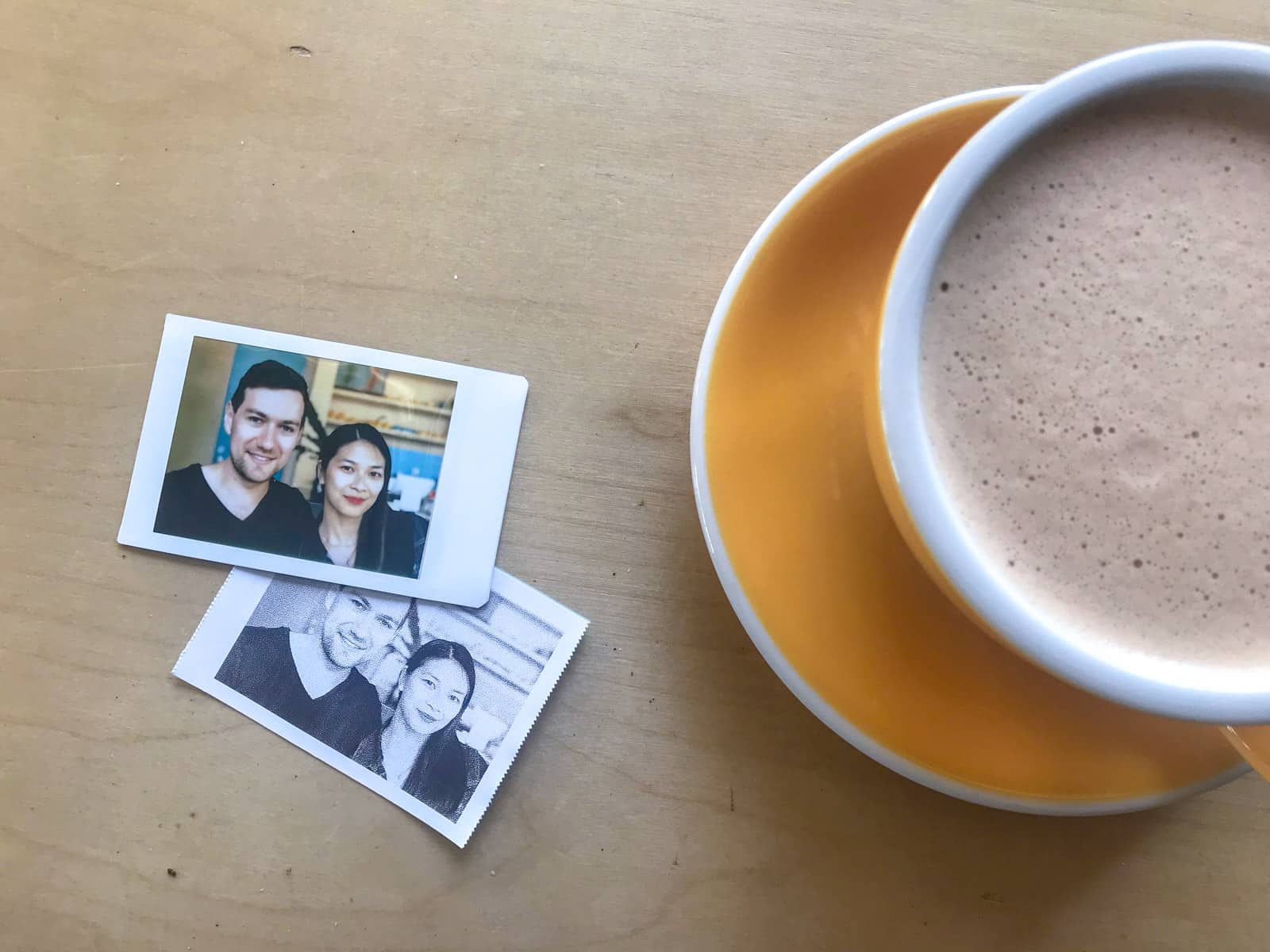A photo of a woman and man printed onto a polaroid, next to a yellow cup of coffee