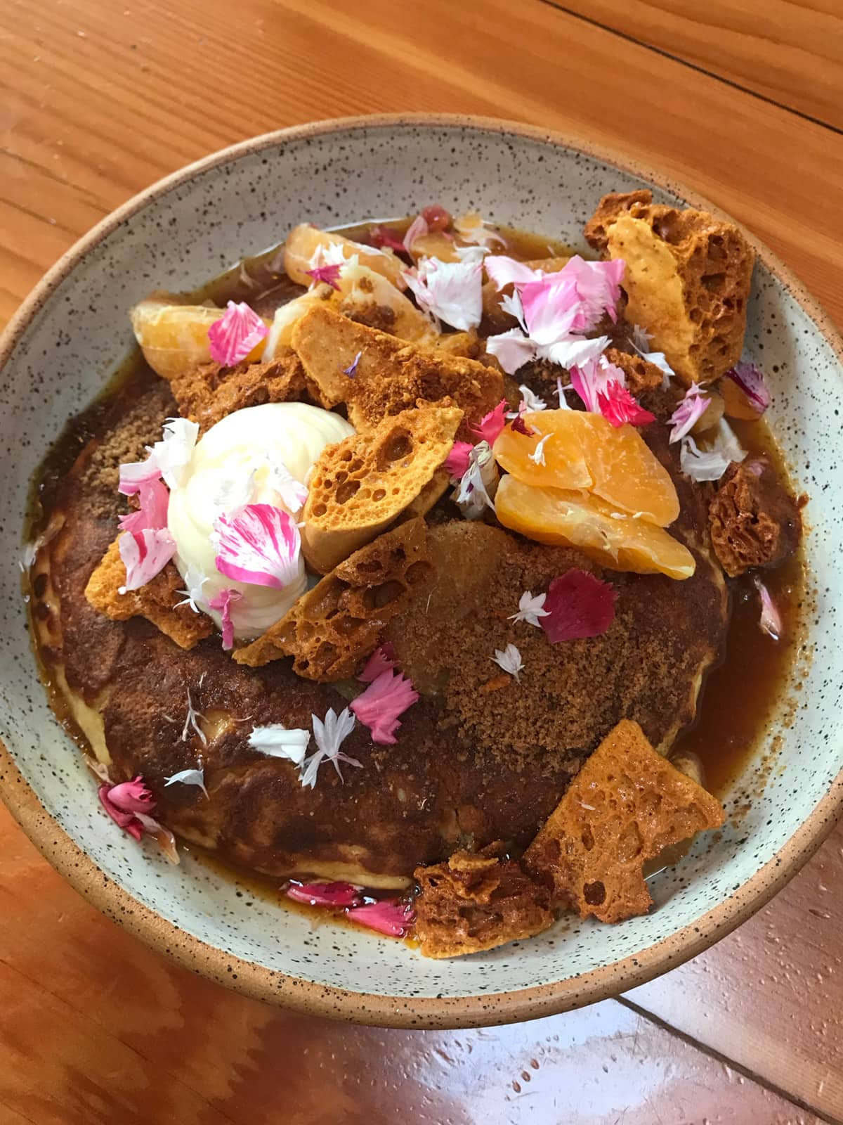 A bowl with hotcakes, decorated with flowers and served with citrus fruit and honeycomb