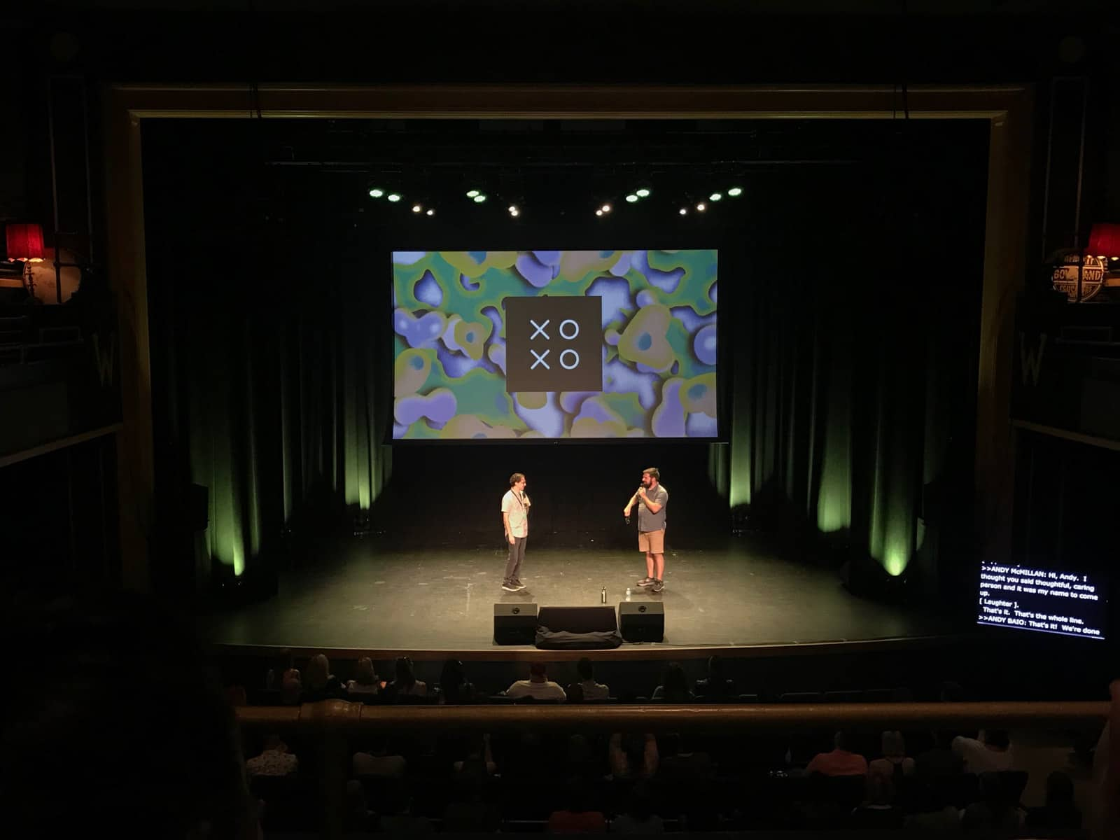 "A stage with two men standing on it, holding microphones, in front of a screen with a coloured pattern and the text ""XOXO"""