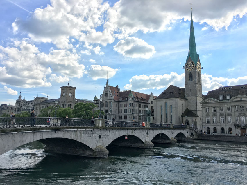 Medium shot of a bridge in Zurich with a tall clock tower