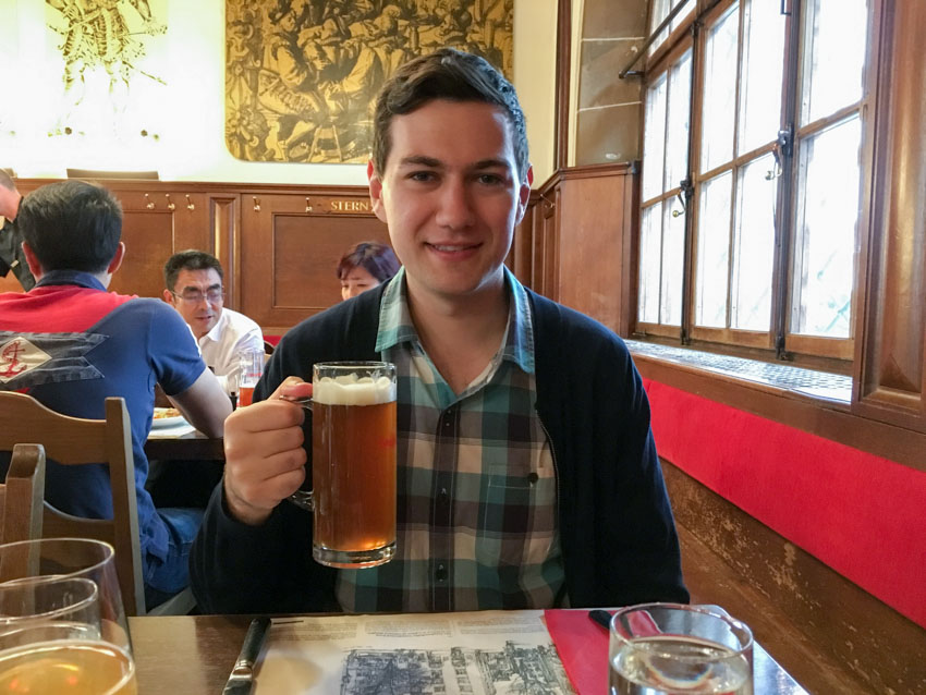 Nick holding up a large mug of house beer