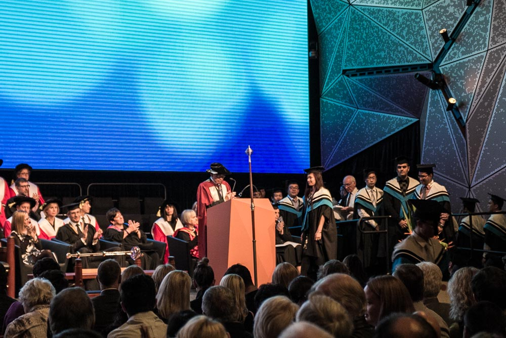 A university graduation ceremony on a stage, viewed from the crowd. Many people in blue gowns are lined up with one woman walking to the podium