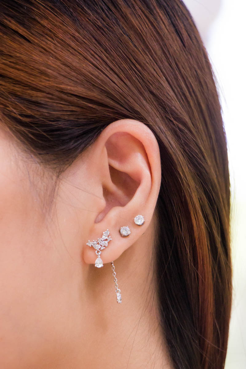 A close-up of the earrings, which have a chain drop backing