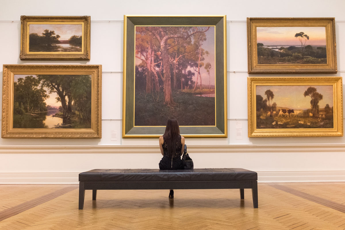 Sitting on a bench in front of a wall of artworks