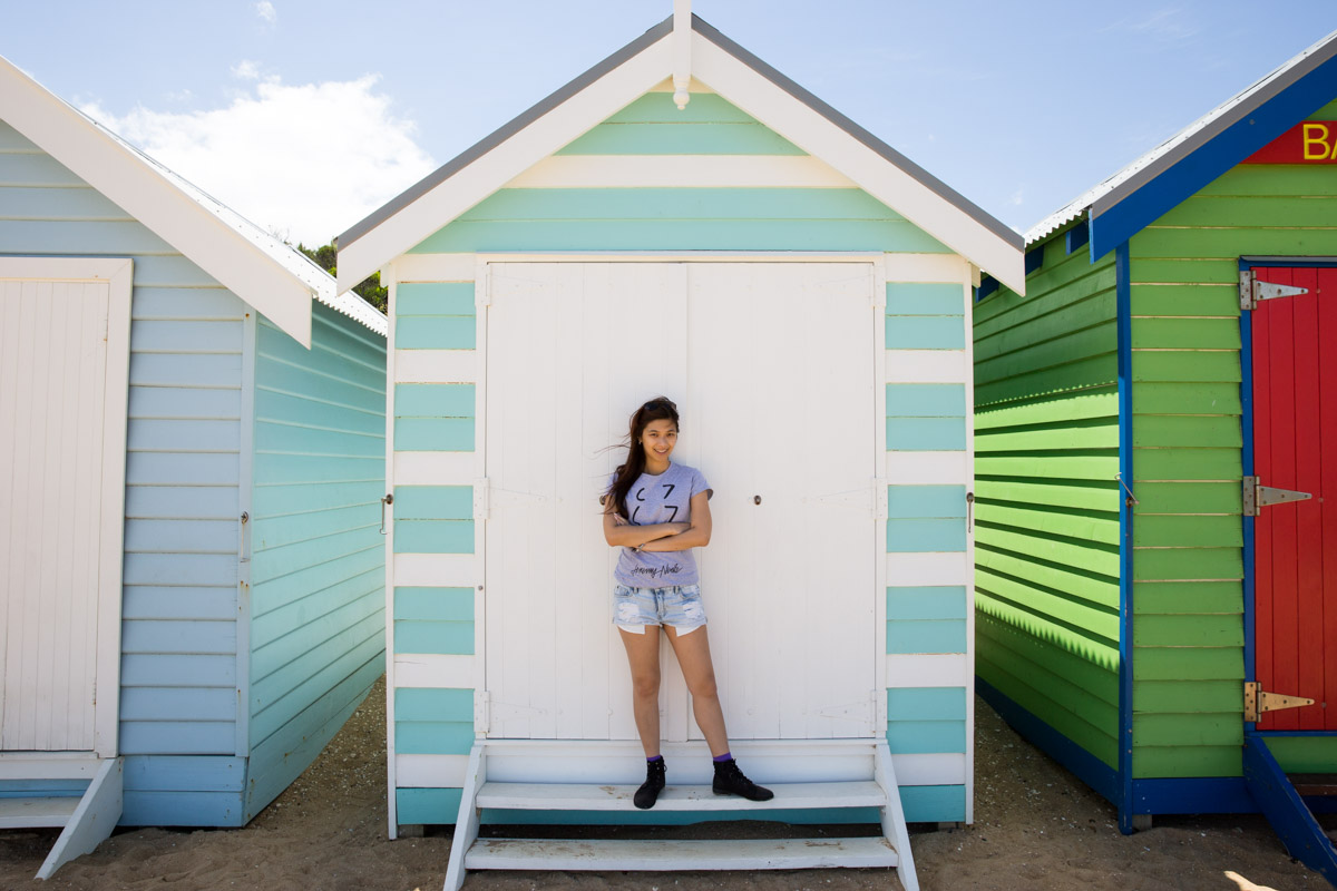 Me standing in front of one of a pale blue and white striped beach hut.