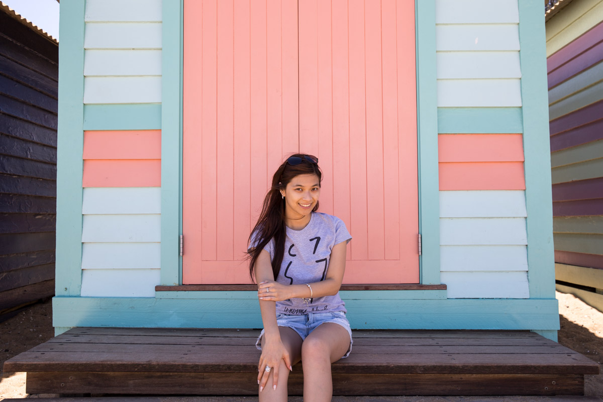 Me sitting in front of a pastel blue and peach-pink hut