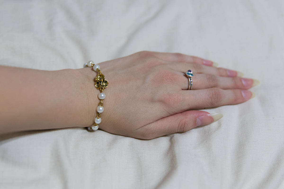 The gold bracelet with white beads on my wrist
