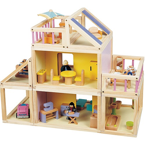 A wooden doll house with furniture, but no doors between the rooms